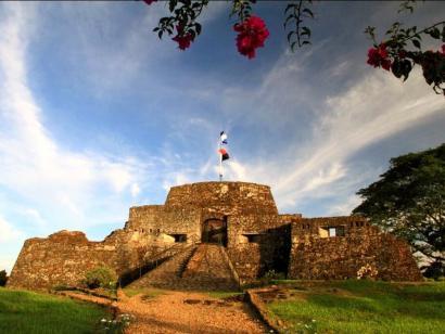 Reise in Nicaragua, Die erleuchtete Kuppel der Kirche La Merced in Granada bei Sonnenuntergang mit Skulpturen der Jungfrau Maria und der Skyline der Stadt in Nicaragua.